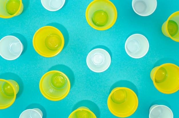 Copos descartáveis de plástico colorido de vista superior Foto gratuita