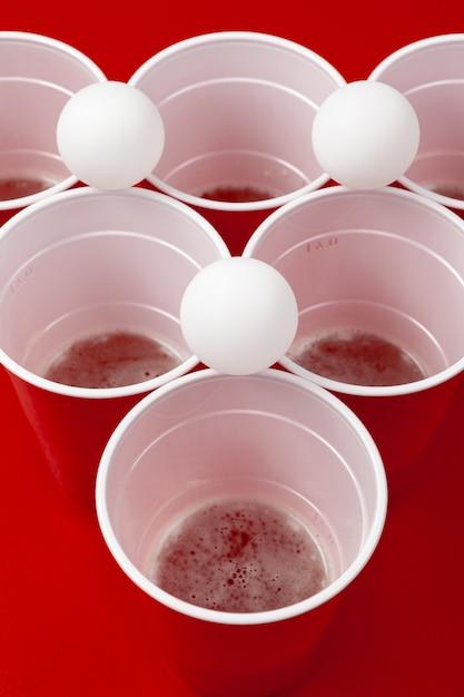 Copos e bola de plástico. jogo de pong de cerveja Foto Premium