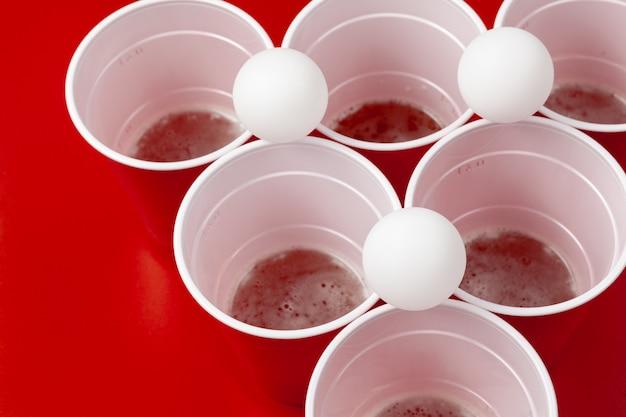 Copos e bola de plástico na superfície vermelha. jogo de pong de cerveja Foto Premium