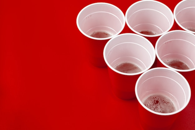 Copos e bola de plástico sobre fundo vermelho. jogo de pong de cerveja Foto Premium