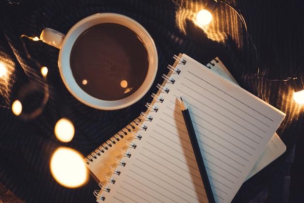 Copos e café são colocados no notebook. Foto Premium