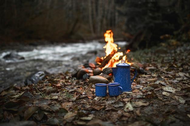 Copos e fogueira perto do riacho Foto gratuita