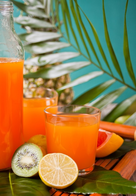 Copos e garrafa de suco multifruit exótico tropical com abacaxi e folha de palmeira no fundo Foto Premium