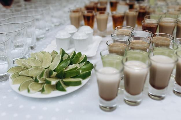 Copos pequenos com bebidas e um prato com limão fatiado Foto gratuita