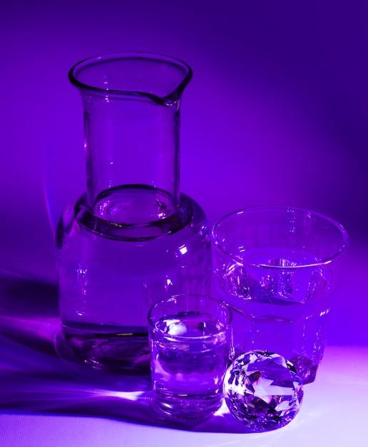 Copos transparentes de água; diamante e copo no contexto roxo Foto gratuita