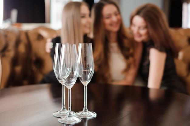 Copos vazios de champanhe no fundo das meninas. Foto Premium