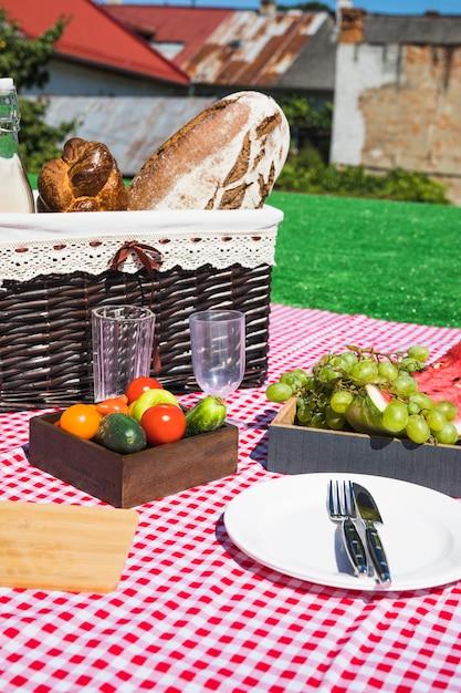 Copos vazios; talheres; frutas e legumes com cesta de piquenique no cobertor Foto gratuita