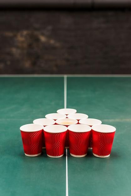 Copos vermelhos na mesa para torneio de cerveja pong Foto gratuita
