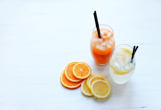 Coquetéis com gelo em copos altos com frutas e tubos de coquetel em um fundo claro Foto Premium