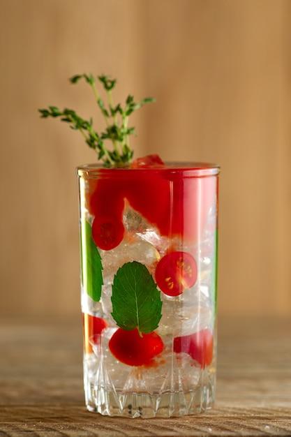 Coquetel com vodka, tomate, hortelã e cubos de gelo na mesa de madeira Foto Premium
