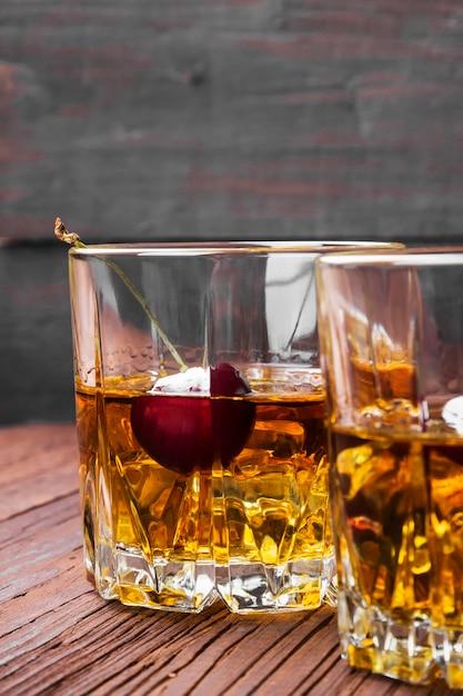 Coquetel de uísque com cereja em dois copos Foto Premium