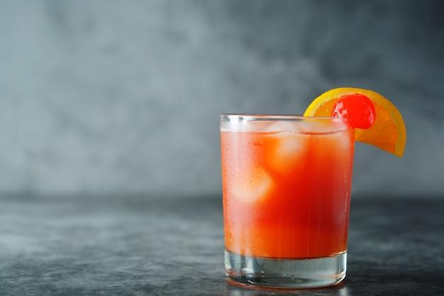 Coquetel de verão. suco de laranja com hortelã, syrop, fatias de frutas e cereja com gelo. Foto Premium