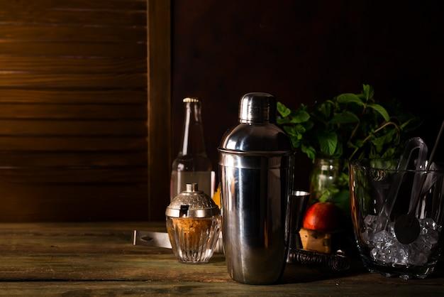 Coqueteleira e açúcar mascavo com gelo em um balde para preparar um coquetel de verão Foto Premium