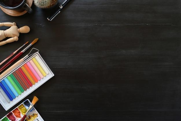 Cor do espaço de trabalho do artista com acessórios criativos na tabela de madeira escura. espaço de trabalho e espaço de cópia. Foto Premium