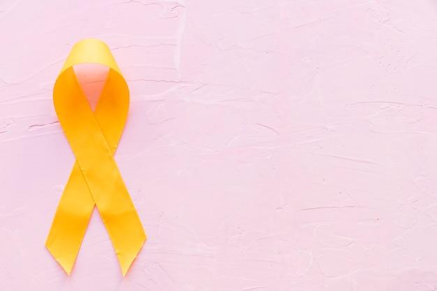 Cor simbólica da fita amarela para o câncer de osso do sarcoma no contexto cor-de-rosa Foto gratuita