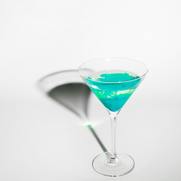 Cor turquesa difusa na água dentro do copo de martini com sombra no fundo branco Foto gratuita