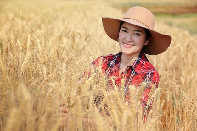 Cor waring da camisa do scoth do fazendeiro da jovem mulher vermelha com o chapéu que senta-se na terra dourada da cevada e muito feliz com produtividade em chiangmai tailândia. Foto Premium