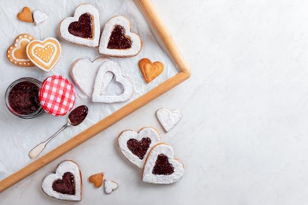 Coração caseiro em forma de biscoitos com geléia de framboesa na mesa branca para o natal ou dia dos namorados. vista do topo. Foto Premium