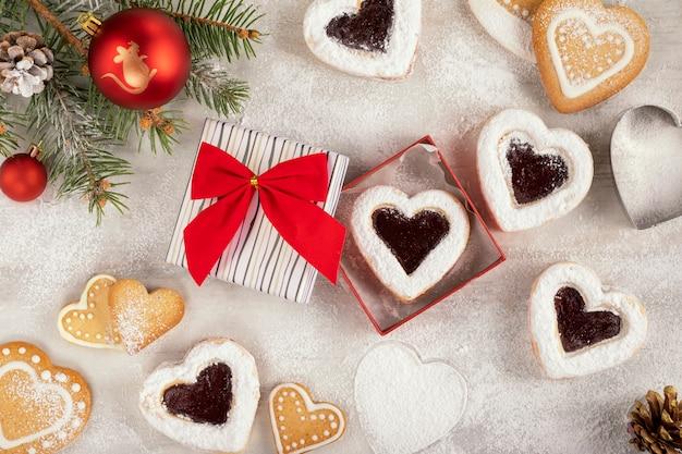 Coração caseiro em forma de biscoitos com geléia de framboesa na mesa de madeira branca para o natal ou dia dos namorados. Foto Premium