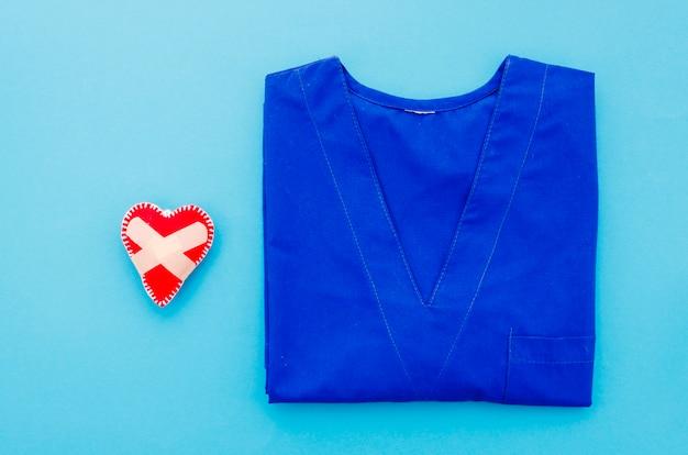 Coração costurada com bandagem adesiva perto do vestido de médico sobre fundo azul Foto gratuita