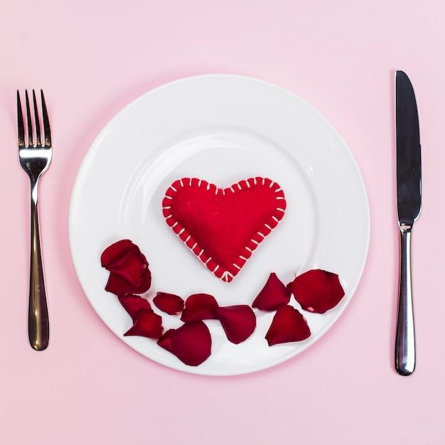 Coração de brinquedo com pétalas de flores na placa Foto gratuita