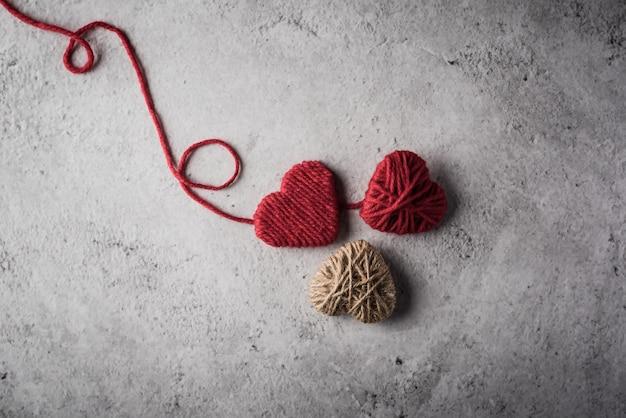 Coração de fio vermelho em forma no fundo da parede Foto gratuita