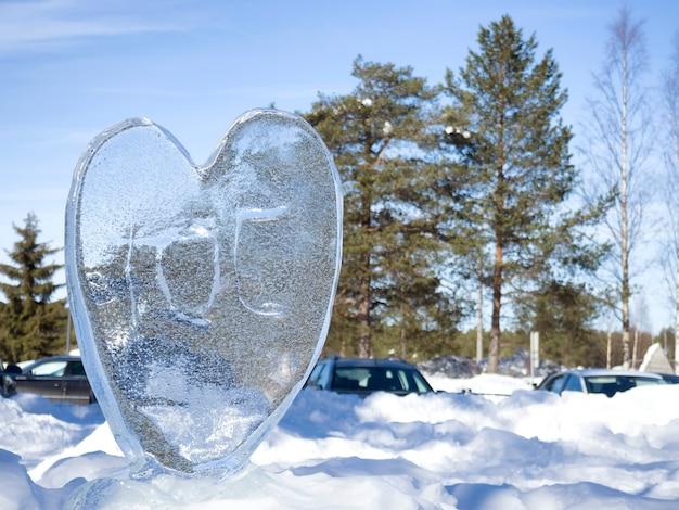 Coração de gelo na neve brilhante com profundidade de campo. Foto Premium