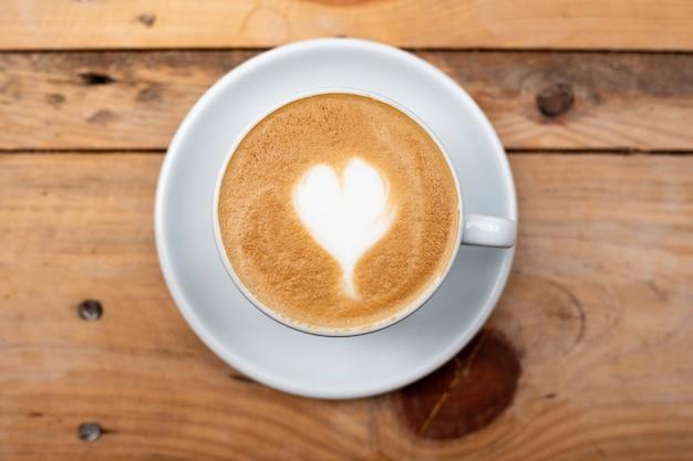 Coração de latte art na mesa de madeira Foto Premium