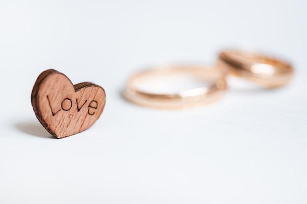 Coração de madeira com amor da inscrição e alianças de casamento dos pares no fundo branco. vista lateral. Foto Premium