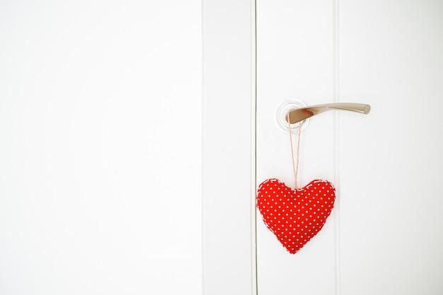 Coração de pano vermelho pendurado na porta Foto Premium