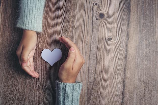 Coração de papel e mãos do casal na mesa de madeira Foto gratuita