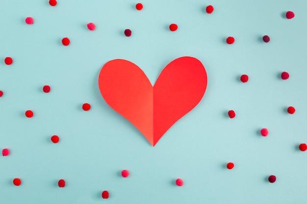 Coração de papel entre confete decorativo Foto gratuita