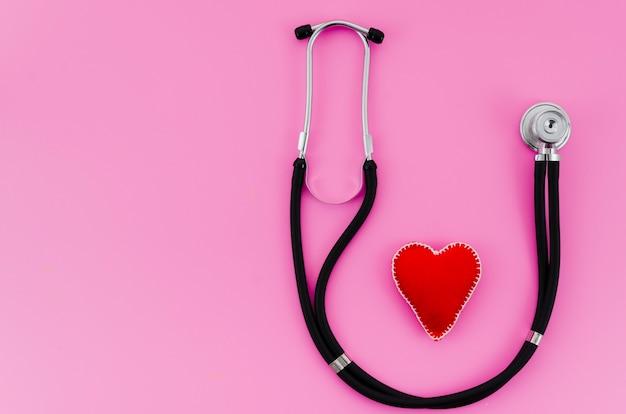 Coração de ponto têxtil vermelho com estetoscópio no fundo rosa Foto gratuita