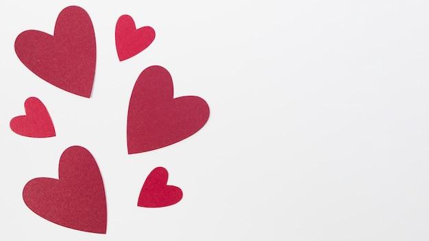 Coração de tamanho diferente de cópia-espaço na mesa Foto gratuita