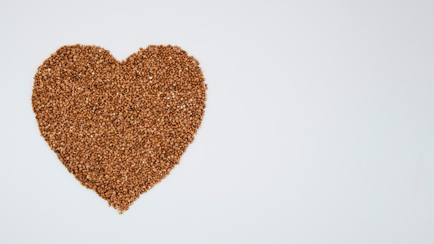 Coração de trigo sarraceno em fundo azul com cópia-espaço Foto gratuita