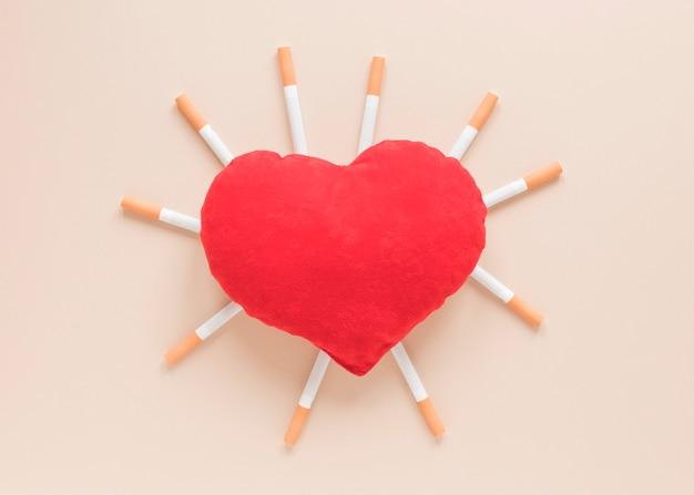 Coração de vista superior rodeado por cigarros Foto gratuita