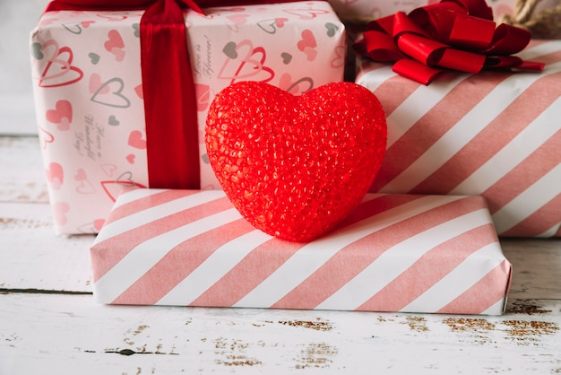 Coração decorativo perto de caixas de presente no envoltório Foto gratuita
