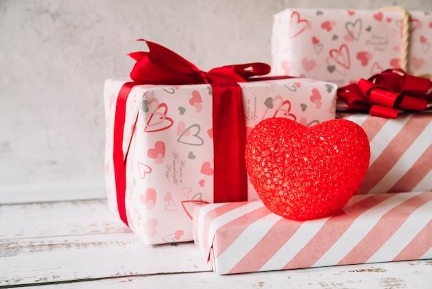 Coração decorativo perto de pilha de caixas de presente no envoltório Foto gratuita