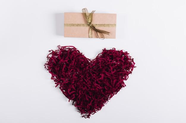 Coração decorativo vermelho e uma caixa com um presente em um fundo branco Foto Premium