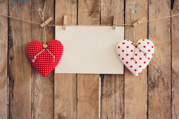 Coração e papel vazio que pendura no fundo de madeira com espaço da cópia. Foto Premium