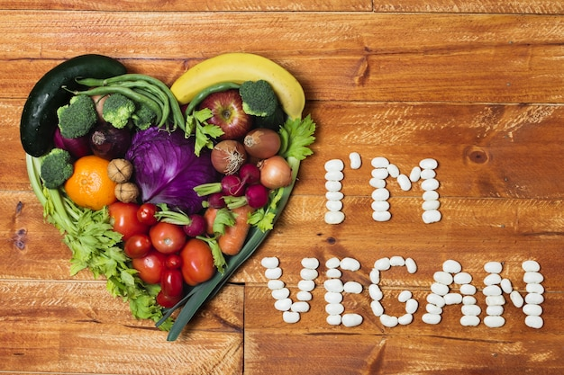 Coração em forma de arranjo de vegetais no fundo de madeira Foto gratuita