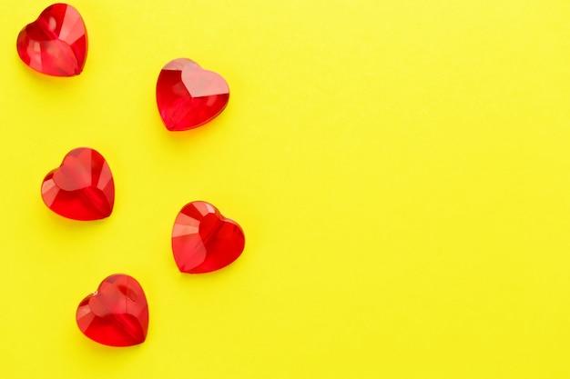 Coração em forma de padrão de cristais vermelhos na superfície amarela Foto Premium