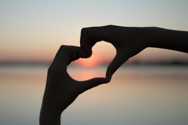 Coração feito com a mão e o sol é o pano de fundo. Foto Premium