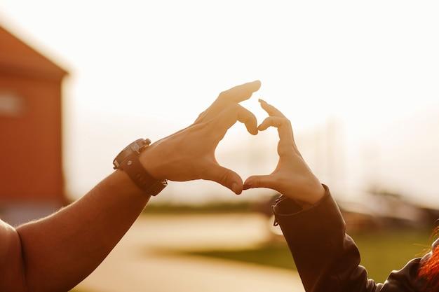 Coração feito das mãos de um cara e uma garota ao pôr do sol Foto Premium