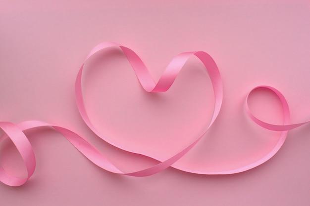 Coração feito de fita rosa em um fundo rosa Foto Premium