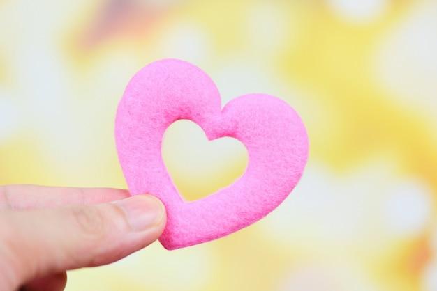 Coração na mão para o conceito de filantropia - homem segurando coração rosa nas mãos para dia dos namorados ou doar ajuda dar amor calor cuidar Foto Premium