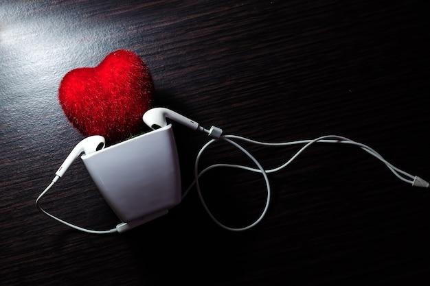 Coração na panela com fone de ouvido branco e mesa de madeira Foto Premium