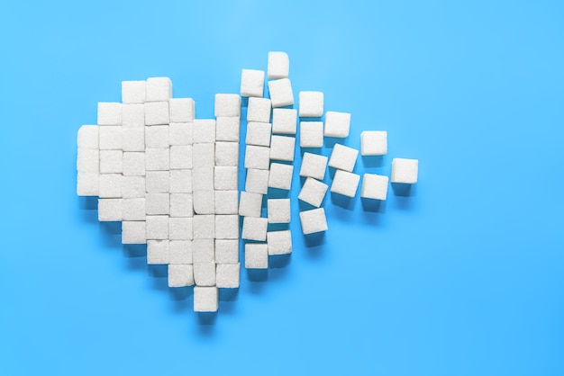 Coração partido de cubos de açúcar branco puro em azul, o dia mundial da luta contra a diabetes Foto Premium