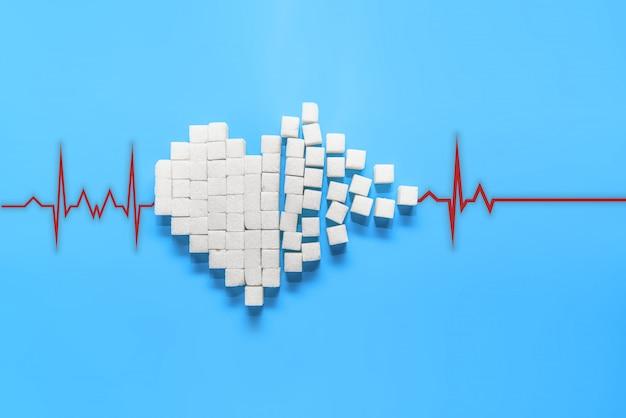 Coração partido de cubos de açúcar branco puro em um fundo azul Foto Premium