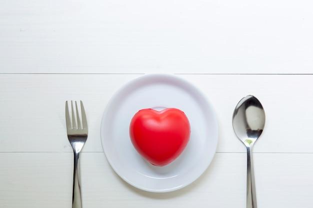 Coração vermelho com amor e prato e colher e garfo no fundo de madeira Foto Premium